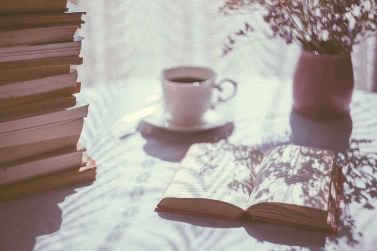 A stack of books, an open book, a mug of coffee, and a vase of flowers